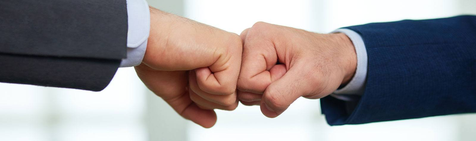 Close-up of hands fist bumping.